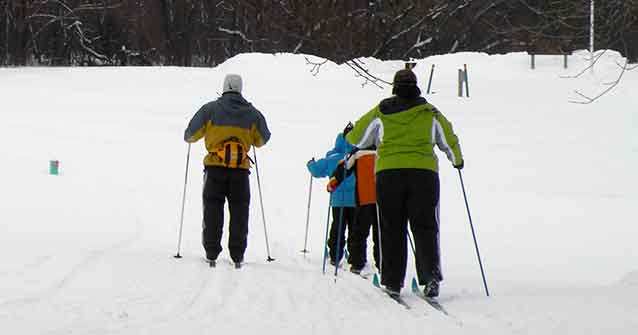 Family of four cross country skiing