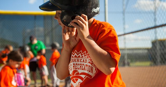 Boy removing his baseball helmet in the dugout